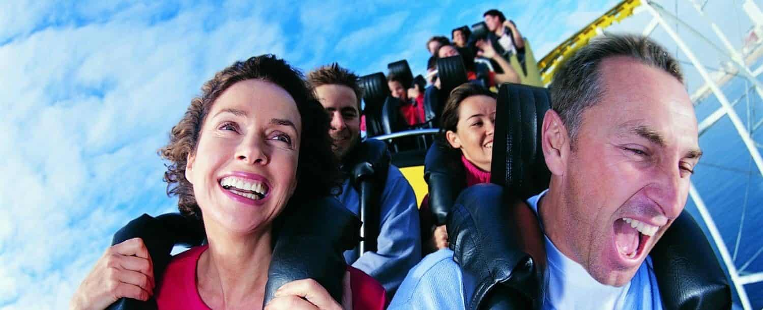People smiling and laughing while riding a rollercoaster