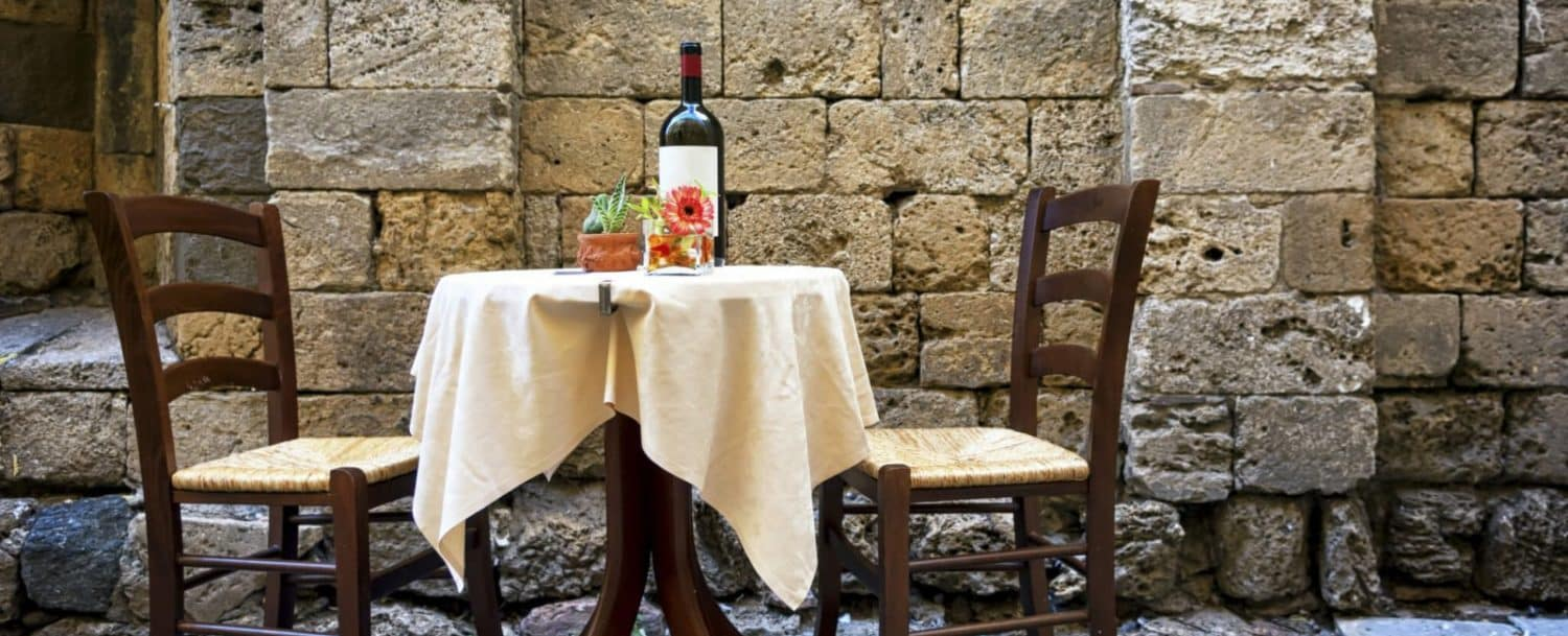 outdoor cafe table with bottle of wine