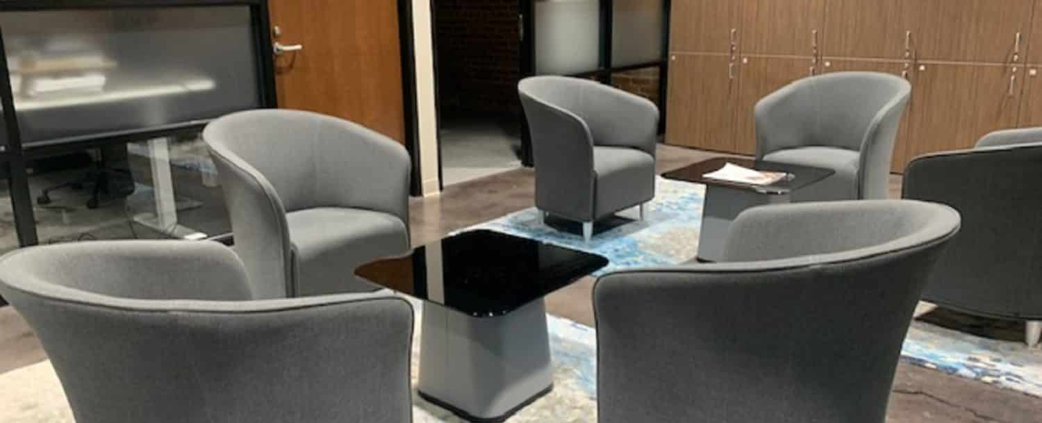 several gray club chairs arounnd a small table in the business discussion space