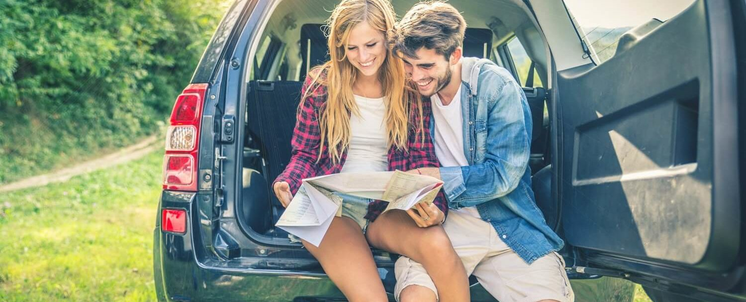couple sitting on truck tailgate looking at road map
