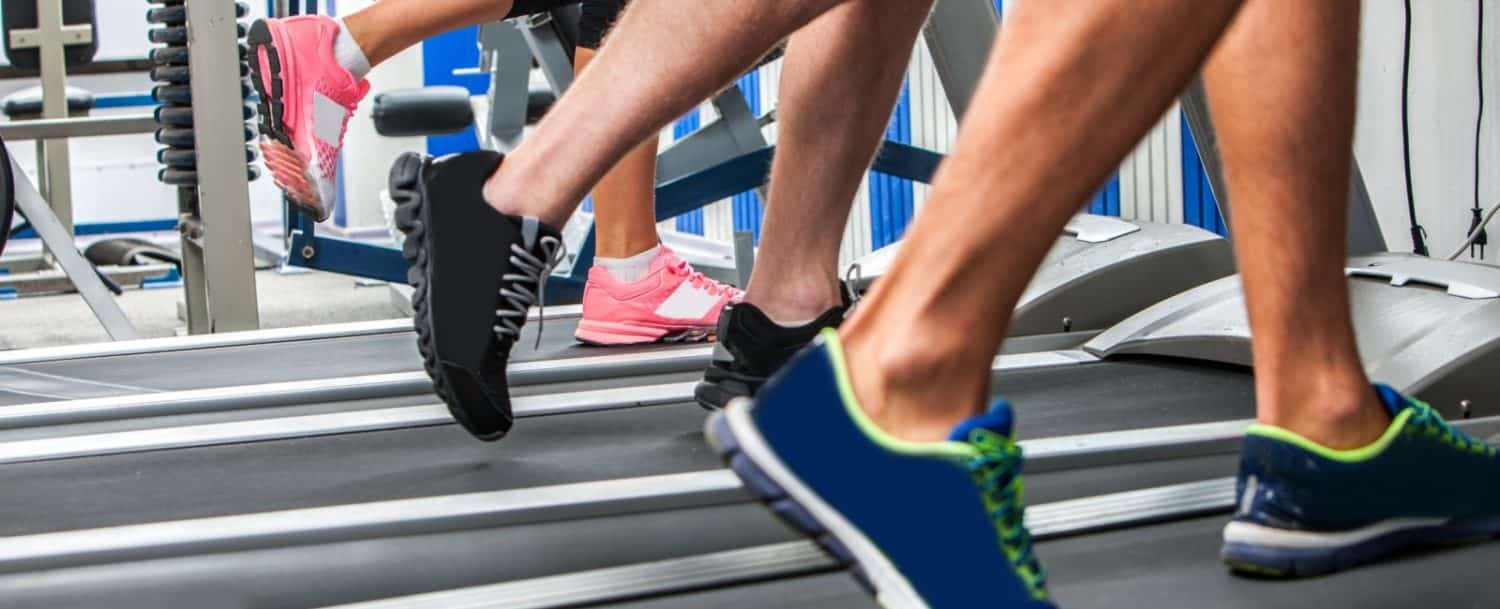 People's legs with sneakers, running on treadmill
