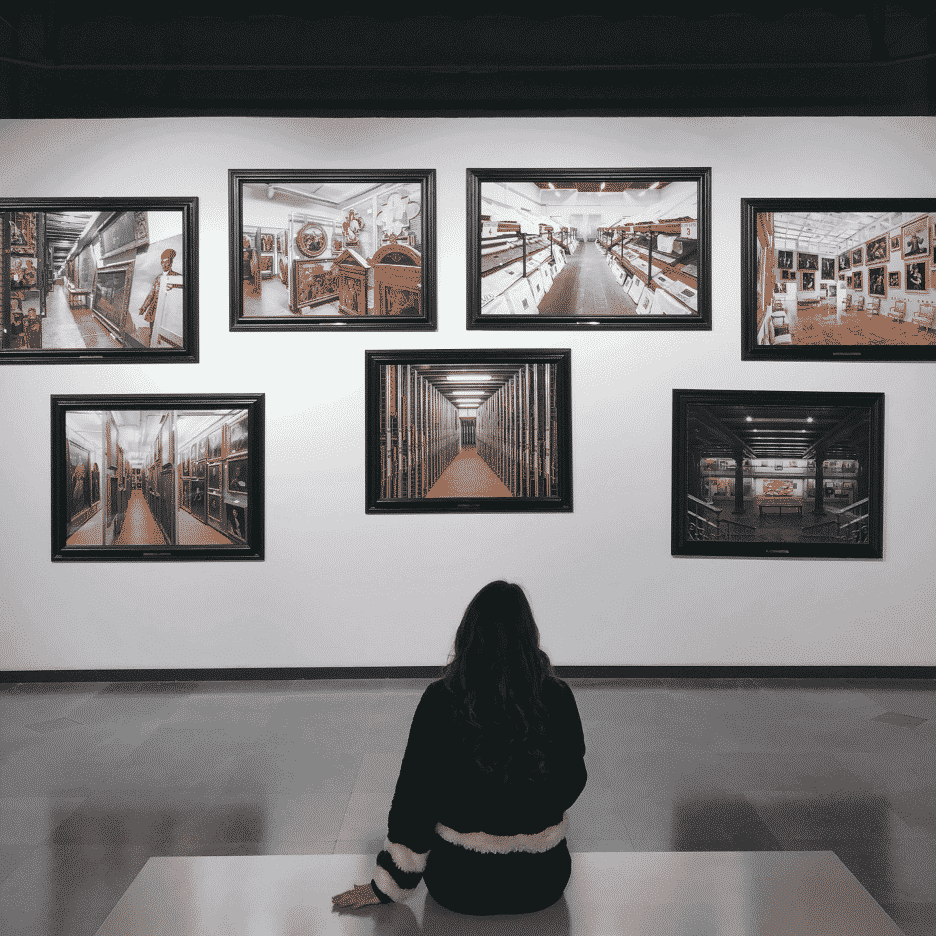 Woman sitting admiring a wall display of photography