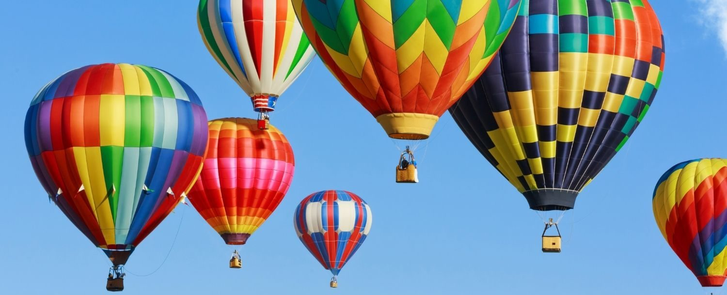 A colorful array of hot air balloons lifting off.