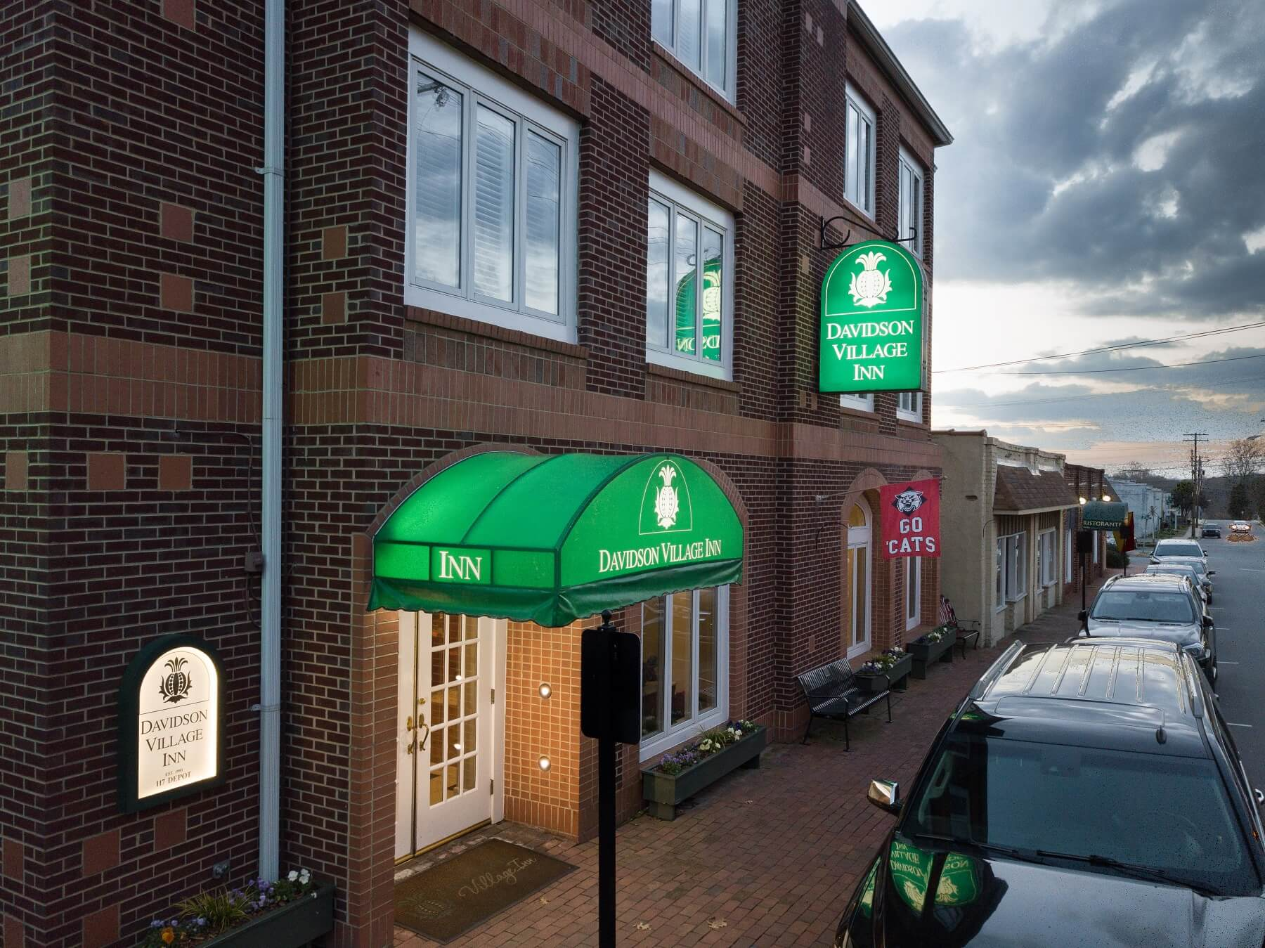 Exterior brick building of Davidson Inn with green awning over entrance