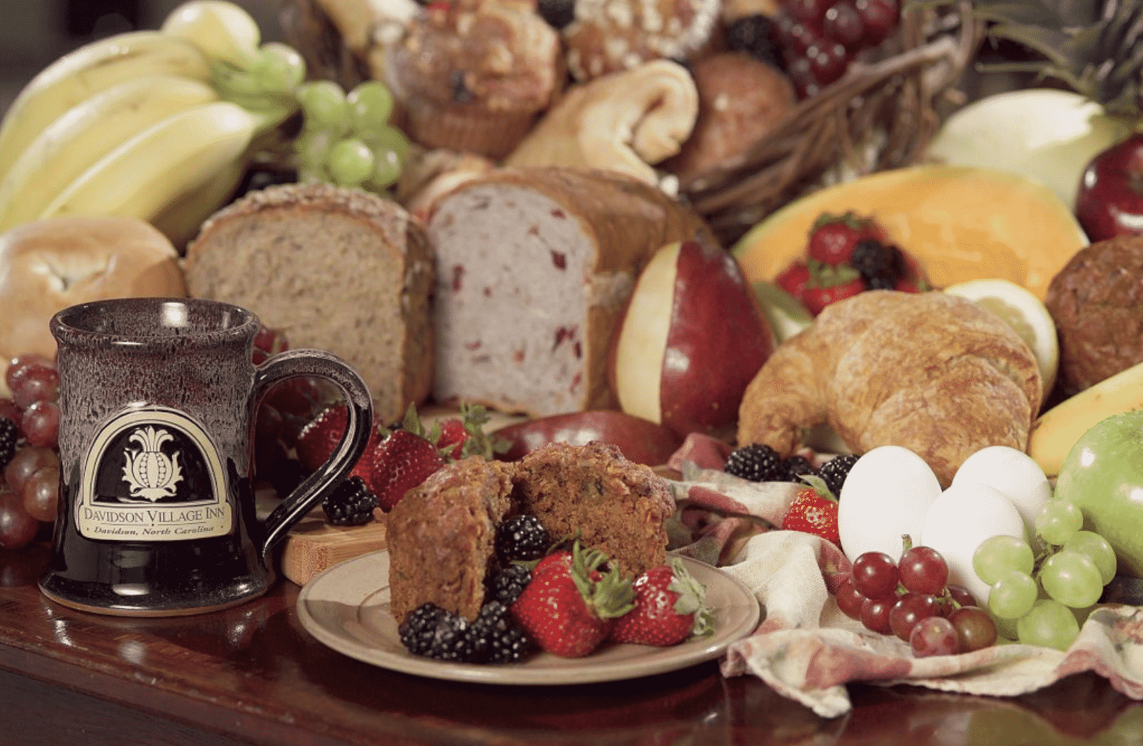 Table topped with a colorful array of breads and fruit for breakfast