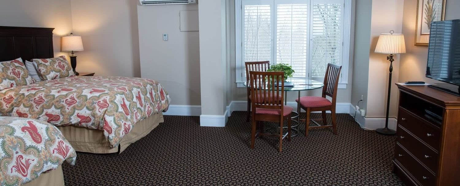Guest room at Davidson Village Inn with two beds, table and three chairs, dresser and TV, and large window