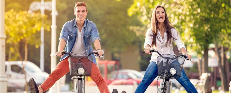 Couple having fun bicycling down the sidewalk