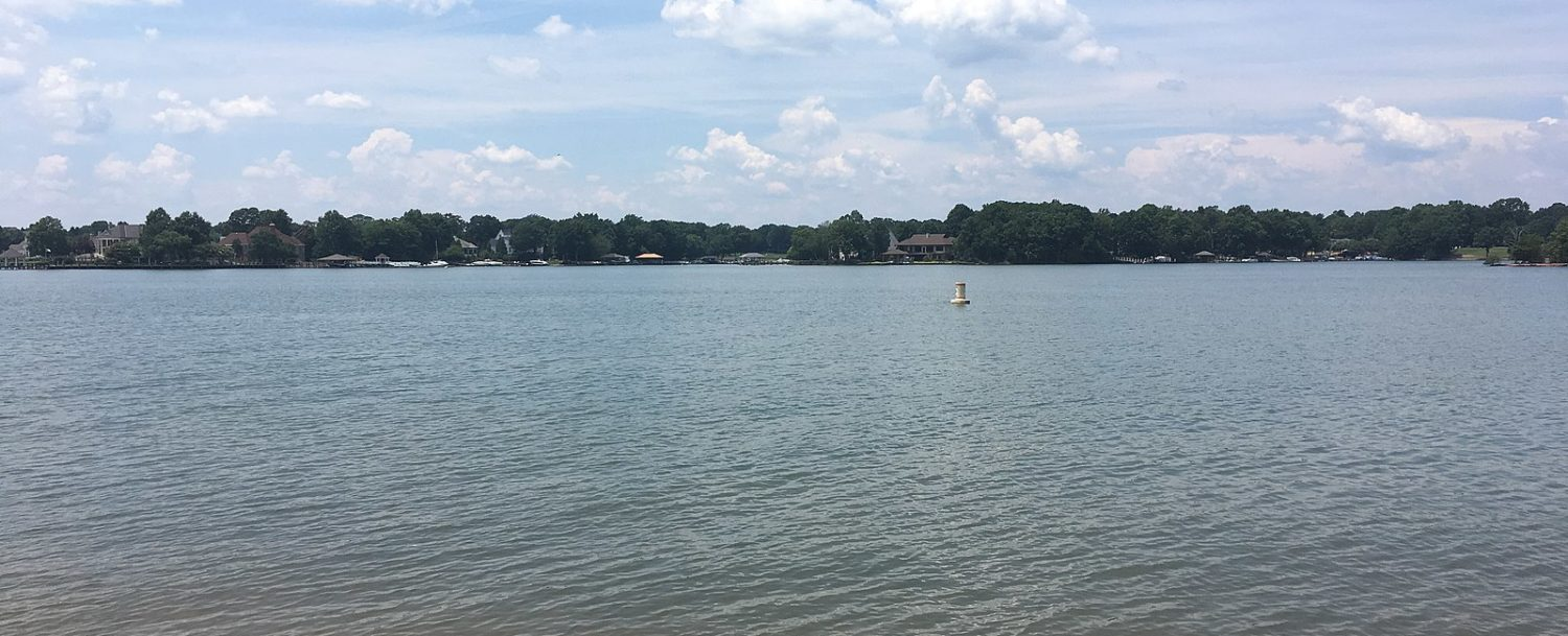 Scenic view of Lake Norman surrounded by trees and houses and blue skies