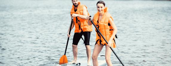 Couple paddle boarding on a lake.