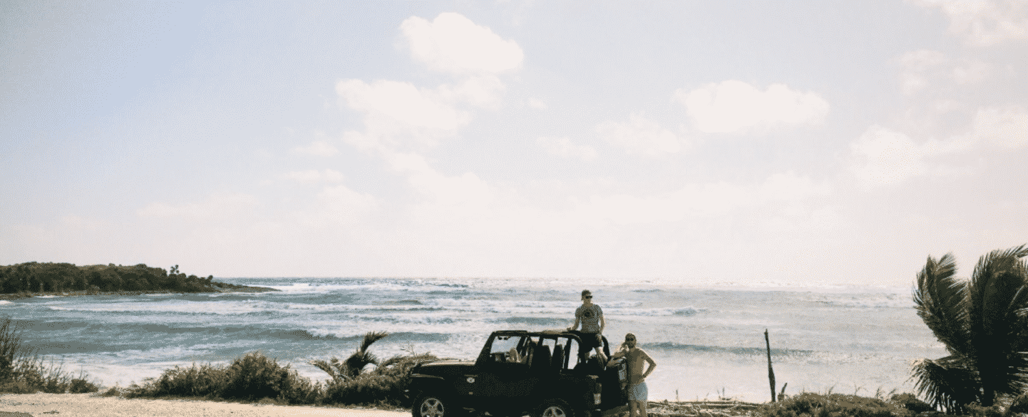 Two people standing by their jeep parked alongside the road near open water