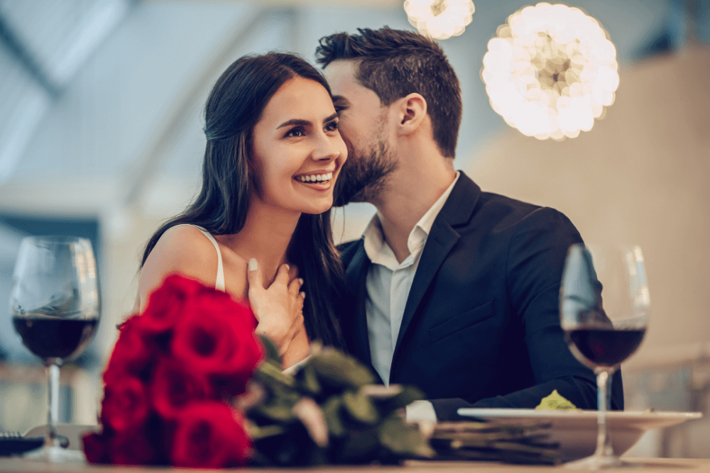 man kissing cheek of woman sitting at table with bouquet of red roses and glasses filled with wine
