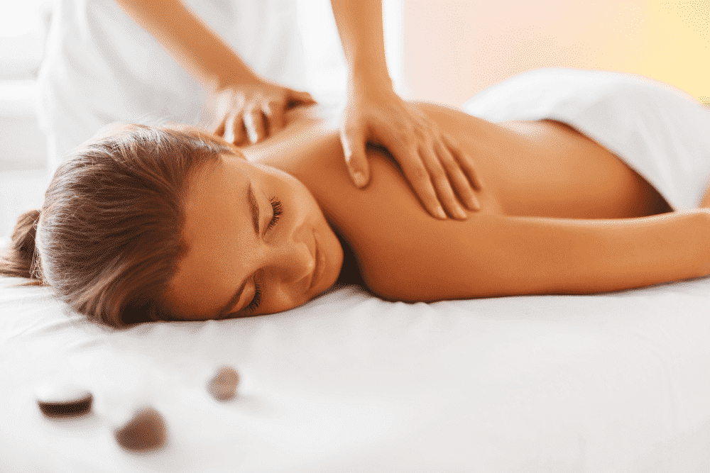 woman with smile getting massage laying face down on table covered with white towel