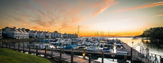 Large marina filled with boats near large body of water with sun setting in the background