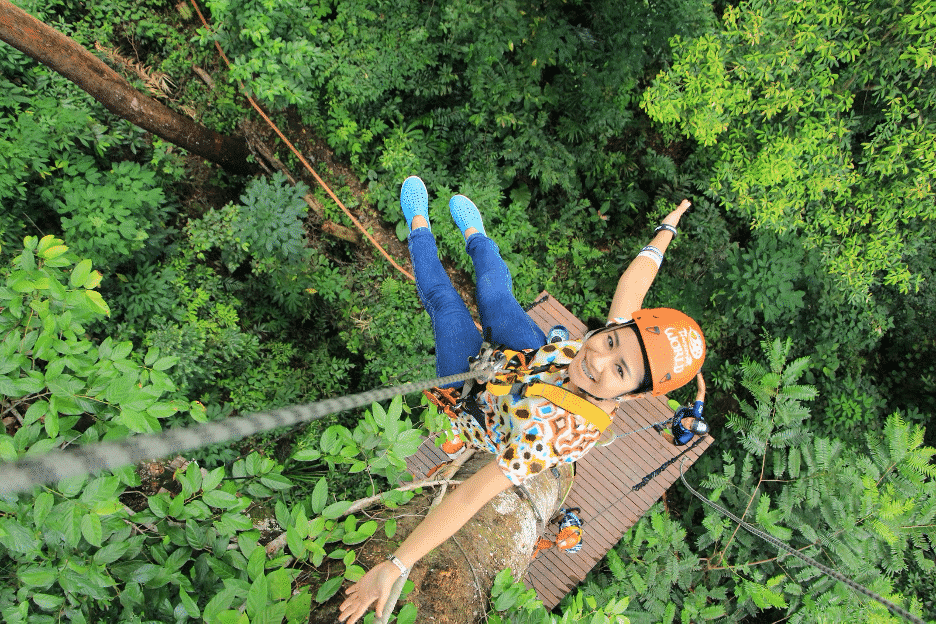 Girl ziplining through the lush green trees